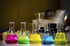 Färgrik lösning i den koniska flaskan som fodras på en bänk i en kemilabb med experiment för organisk kemi för suddighetsbakgrund royaltyfri bild