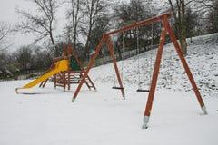 Färgrik lekplats i en parkera under snöstorm Arkivbilder