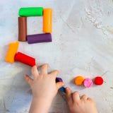Färgrik leraplasticine som modellerar lera som förläggas som fyrkant med barns händer, fyrkant, utbildning, barnpsykologi arkivfoto