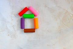Färgrik leraplasticine som modellerar lera som förläggas som hus på cementbakgrund som är horisontal, utbildning, barnpsykologi arkivbild