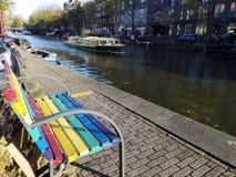 Färgrik LGBT-bänkstolthet, kanaler och hus av den Amsterdam staden, i Holland, Nederländerna royaltyfri foto