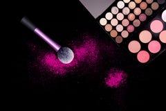 Färgrik makeuppalett och rosa stor borste som applicerar pulver på ren svart bakgrund Yrkesmässig makeuputrustning arkivfoto