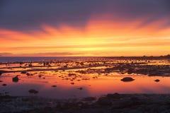 Färgrik och mycket ljus solnedgång på havet på lågvatten Arkivbild