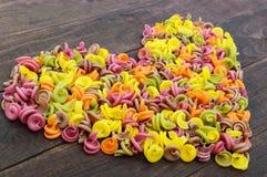 Färgrik pasta som färgas av grönsakbeta, gräsplaner, spenat, morötter, tomater, peppar på en mörk trätabell i form av hjärta Arkivbild