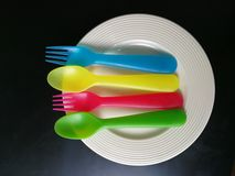 Färgrik plast- sked och gaffel på den vita maträtten Royaltyfri Foto