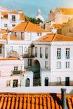 Färgrik röd och vit citycape av Lissabon Historiskt centrum som byggs på sidan av kullen Ljus solig sommardag fotografering för bildbyråer