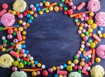 Färgrik ram av mångfärgade godisar på svart träbakgrund royaltyfri foto
