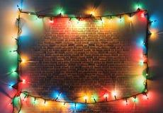 Färgrik ram för julljus på retro bakgrund för tegelstenvägg Royaltyfri Foto