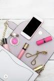 Färgrik ram med olika makeupprodukter på vit träbaksida Fotografering för Bildbyråer