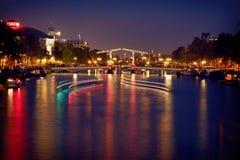 Färgrik reflexion av den Magere Brug bron i Amsterdam på natten Royaltyfri Fotografi