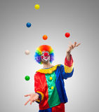 Färgrik rolig clown som jonglerar bollar Arkivfoto