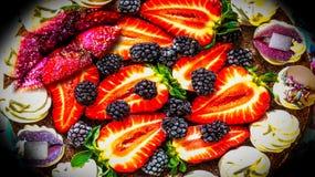 Färgrik rolig jordgubbekaka och sockerkanter arkivbild