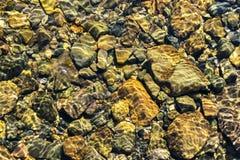 Färgrik Rolling Stone modell med lugnt vatten Färgrika havsstenar under lugnt vatten Regnbågsskimrande solljus på stenarna Transp Arkivbilder