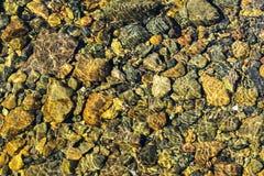 Färgrik Rolling Stone modell med lugnt vatten Färgrika havsstenar under lugnt vatten Regnbågsskimrande solljus på stenarna Transp Royaltyfri Foto