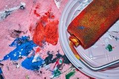 Färgrik rulle som ligger på den vita plattan efter beign som används för väggkonstmålning royaltyfri fotografi