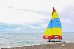 Färgrik segelbåt på stranden på en molnig dag royaltyfri foto