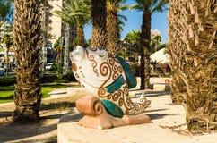 Färgrik skulptur av fisken som målas med blom- modeller in i beiga och gräsplan, tonar, Eilat, Israel Arkivfoton