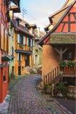 Färgrik slingrig gata med gamla hus som dekoreras för jul, Eguisheim, nord-östliga Frankrike royaltyfria foton