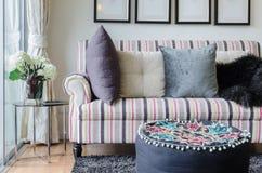 Färgrik soffa med kuddar och exponeringsglastabellen i vardagsrum royaltyfria foton