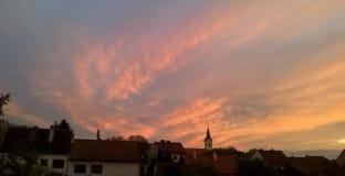 Färgrik solnedgång över liten by arkivbilder