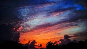 färgrik solnedgång BERÄTTELSE BAK MOLN arkivbild
