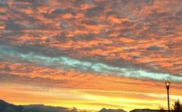 Färgrik solnedgång från gatan med lyktstolpen och berg Royaltyfria Bilder