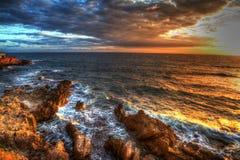 Färgrik solnedgång i Alghero den steniga kustlinjen Royaltyfria Bilder