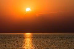 Färgrik solnedgång i havet med reflexioner och moln arkivbilder