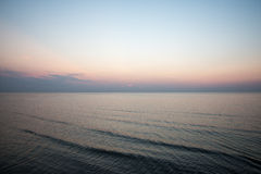 Färgrik solnedgång i havet med reflexioner och moln royaltyfri foto
