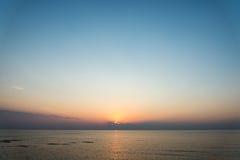Färgrik solnedgång i havet med reflexioner och moln royaltyfri bild