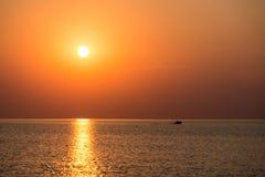 Färgrik solnedgång i havet med reflexioner och moln royaltyfria bilder