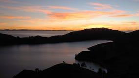 Färgrik solnedgång med orange himmel som refelcting i sjön Titicaca arkivbild
