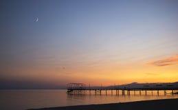 Färgrik solnedgång och måne från den over pir fotografering för bildbyråer