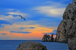 Färgrik solnedgång på den steniga kusten av Blacket Sea, Krim, Novy Svet Arkivfoton