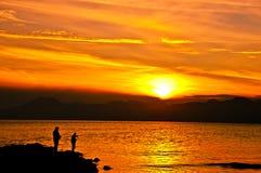Färgrik solnedgång på havet med fiskarekonturer Arkivbilder