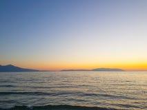 Färgrik solnedgång på seacoasten ingen molnsommartid Arkivbilder