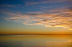 Färgrik solnedgång vid ett absolut lugna vatten Arkivbilder