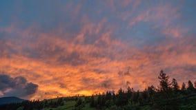 Färgrik solnedgånghimmel- och molnaftonrodnad Solinställning ovanför schackningsperiod för bergkonturtid arkivfilmer