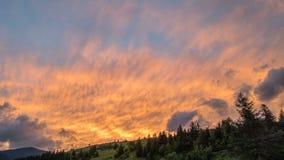 Färgrik solnedgånghimmel- och molnaftonrodnad Solinställning ovanför schackningsperiod för bergkonturtid lager videofilmer