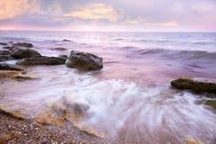 Färgrik soluppgång över havet och Rocky Coastline, flödande wa Arkivfoto