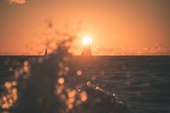 färgrik soluppgång över sjön med det lilla fartyget - tappningeffekt arkivfoton