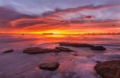Färgrik soluppgång eller solnedgången på en djupfryst sjö med vaggar Royaltyfria Foton