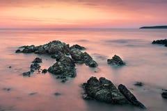 Färgrik soluppgånghorisont som beskådas från stranden, vaggar Royaltyfria Bilder