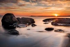 Färgrik soluppgånghorisont som beskådas från stranden, vaggar Arkivbilder