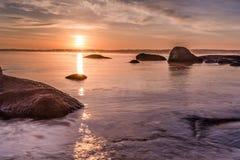 Färgrik soluppgånghorisont som beskådas från stranden, vaggar Arkivfoto