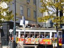 Färgrik spårvagnbil med turister i Lissabon Arkivbild