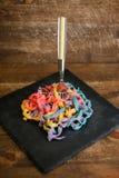 Färgrik tagliatelle med gaffeln på den svarta plattan arkivfoton