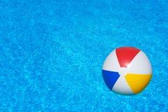 Färgrik uppblåsbar boll som svävar i simbassäng Royaltyfria Bilder