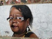 Färgrik väggmålning av gatakonst om en bedöva afrikansk amerikankvinna arkivbild
