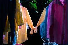 Färgrik våt kläder som hänger på stålklädstrecket för att torka vid värmen av solen fotografering för bildbyråer